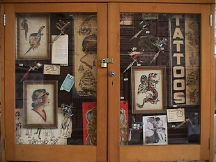 "Display case holding various antique machines, Doc Forbes pre-WW II flash, Sailor Pancho ""Tattoos window Sign"""